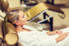 Beautiful young woman sitting in bath robe at spa Royalty Free Stock Images