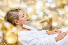 Beautiful young woman sitting in bath robe at spa Stock Photography