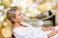 Beautiful young woman sitting in bath robe at spa Stock Photos