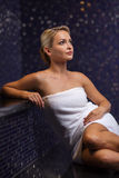 Beautiful young woman sitting in bath towel. People, beauty, spa, healthy lifestyle and relaxation concept - beautiful young woman sitting in bath towel Royalty Free Stock Photography