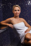 Beautiful young woman sitting in bath towel. People, beauty, spa, healthy lifestyle and relaxation concept - beautiful young woman sitting in bath towel Royalty Free Stock Photos
