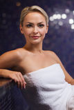 Beautiful young woman sitting in bath towel Stock Image