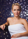 Beautiful young woman sitting in bath towel Royalty Free Stock Images