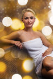 Beautiful young woman sitting in bath towel Stock Images