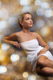 Beautiful young woman sitting in bath towel Royalty Free Stock Photos