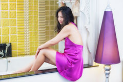 Beautiful young woman sitting by the bathtub stock image