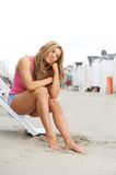 Beautiful young woman sitting at the beach with barefeet in sand Stock Photo