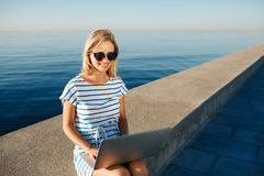 Beautiful young woman sitting on beach with laptop smiling and c. Ommunicates over the Internet via Wi Fi Royalty Free Stock Images