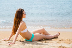 Beautiful young woman sitting on the beach Stock Image