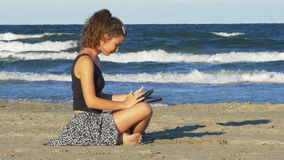 Beautiful young woman sitting on the beach and tipping on her tablet pc on a summer day. Beautiful young woman sitting on the beach and tipping on her tablet pc stock video footage