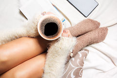 Beautiful young woman sitting in bed with cup of coffee Stock Images