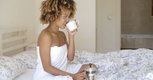 Beautiful young woman sitting in bed. Exotic Girl pouring freshly brewed coffee to a classic cup Stock Images