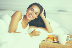 Beautiful young woman sitting in bed and having breakfast Stock Photography