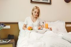 Beautiful young woman sitting on bed and having breakfast. Beautiful young woman traveller sitting on bed in hotel room in the morning and having breakfast, copy Stock Photos