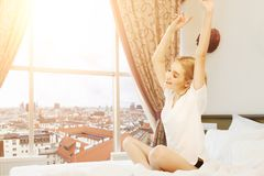 Beautiful young woman sitting on bed and listening to music. Beautiful young woman traveller sitting on bed in hotel room with city view and listening to Stock Photos