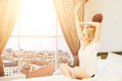 Beautiful young woman sitting on bed and listening to music. Beautiful young woman traveller sitting on bed in hotel room with city view and dancing, having fun Royalty Free Stock Photo