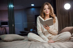 Beautiful young woman sitting on the bed and reading Stock Photography