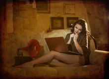 Beautiful young woman sitting on bed working on laptop having a red gramophone near her, in boudoir scenery. Attractive brunette Royalty Free Stock Images