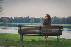 Beautiful young woman sitting on a bench in a city park Royalty Free Stock Photos