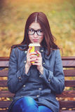Beautiful young woman sitting on a bench drinking coffee or hot tea in the spring  autumn coat enjoying in park outdoor Stock Images