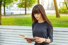 Beautiful young woman sitting on a bench in the street reading a book stock image