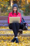Beautiful young woman sitting in a bench and using her laptop in autumn. Portrait of beautiful young woman sitting in a bench and using her laptop in autumn Stock Photos