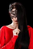 Beautiful young woman sitting in a black mask Stock Photos