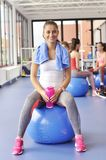 Beautiful young woman sitting on the blue pilates ball Stock Photography