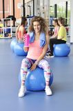 Beautiful young woman sitting on the blue pilates ball Stock Image