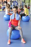 Beautiful young woman sitting on the blue pilates ball Royalty Free Stock Photo