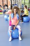 Beautiful young woman sitting on the blue pilates ball Royalty Free Stock Image