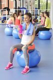 Beautiful young woman sitting on the blue pilates ball Stock Photos
