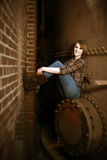 Beautiful Young Woman Sitting by Boiler. A beautiful young woman sitting on an iron wall Stock Images