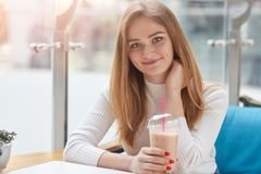 Beautiful young woman sitting in cafe with fresh cocktail, having rest after lectures, looks smiling at camere, keeps hand on neck stock images