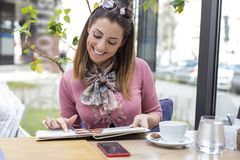 Beautiful young woman sitting in a cafe while reading the menu. And smiling royalty free stock photography