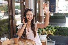 Beautiful young woman sitting at the cafe table outdoors royalty free stock images