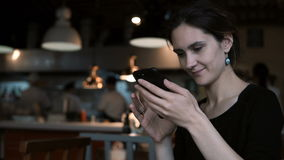 Beautiful young woman sitting in cafe and using the smartphone. Attractive female typing message on touchscreen. Brunette girl spending leisure time in social stock footage