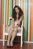Beautiful young woman sitting on chair against colorful striped wall Stock Photo