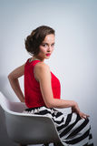 Beautiful young woman sitting in the chair gracefully Royalty Free Stock Photos