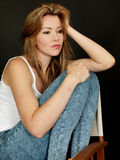 Beautiful Young Woman Sitting in a Chair with thoughtful Expression Stock Photo