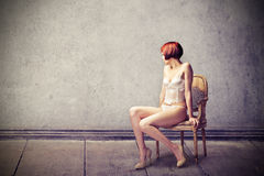 Beautiful young woman sitting on a chair Stock Images