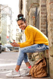 Beautiful young woman sitting by a city street Stock Photos