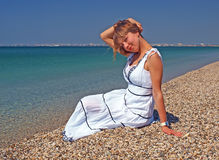 Beautiful young woman sitting on a coastline Royalty Free Stock Image