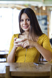 Beautiful young woman sitting in a coffee shop and drink tea Stock Image
