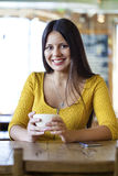 Beautiful young woman sitting in a coffee shop and drink tea Stock Photo