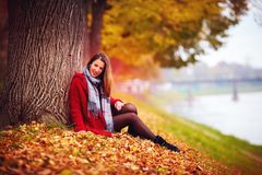 Beautiful young woman sitting in fallen leaves at autumn park. Beautiful young woman sitting in colorful fallen leaves at autumn park Royalty Free Stock Photo