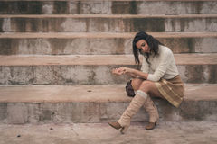 Beautiful young woman sitting on concrete steps Royalty Free Stock Images