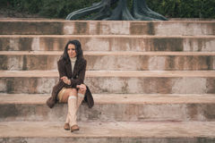 Beautiful young woman sitting on concrete steps Stock Photos