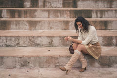 Beautiful young woman sitting on concrete steps Royalty Free Stock Photo