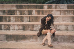 Beautiful young woman sitting on concrete steps Stock Photography